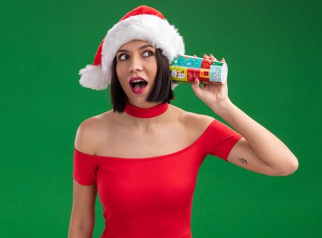 Neugieriges junges mädchen, das weihnachtsmütze hält, das plastikweihnachtsbecher neben ohr hört, das gespräch hört, das seite lokalisiert auf grünem hintergrund betrachtet