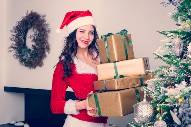 Neugieriges junges sankt-mädchen, weihnachtshut, der kasten mit geschenkgeschenk auf grauem wandhintergrund hält. frohes neues jahr-feier-feiertags-party-konzept.