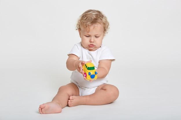 Neugieriges kind, das mit spielzeug spielt, während auf boden sitzt