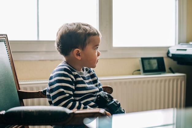 Neugieriges kind erforscht kamera, die auf einem stuhl sitzt