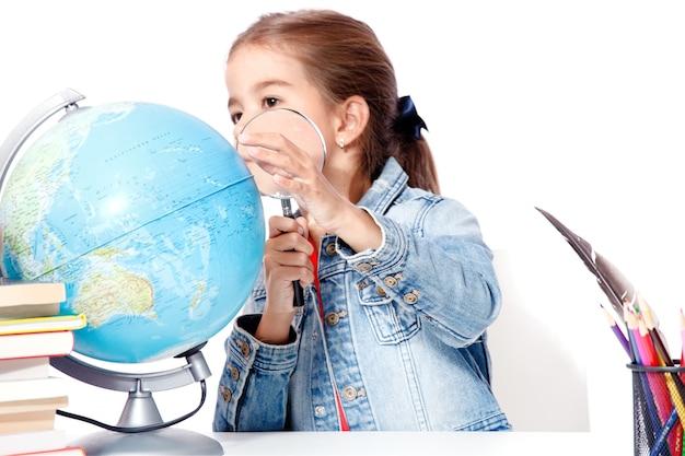 Neugieriges kleines mädchen, das durch die lupe auf dem globus schaut
