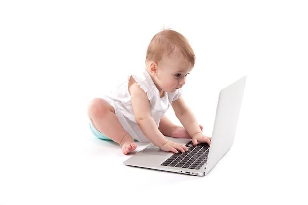 Neugieriges lächelndes kind, das nahe dem laptop sitzt
