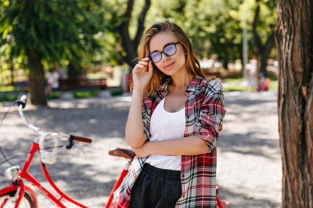 Neugieriges mädchen in der frühlingskleidung, die neben fahrrad steht. attraktive kaukasische dame, die mit fahrrad im park aufwirft.
