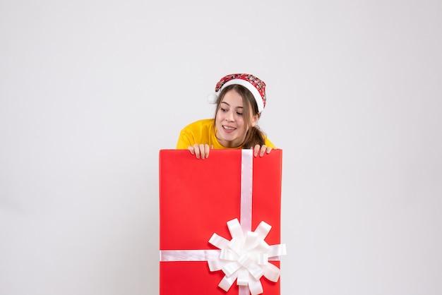 Neugieriges mädchen mit der weihnachtsmütze, die etwas betrachtet, das hinter großem weihnachtsgeschenk auf weiß steht