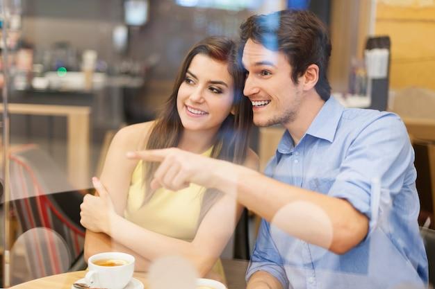 Neugieriges paar, das durch fenster im café wegschaut