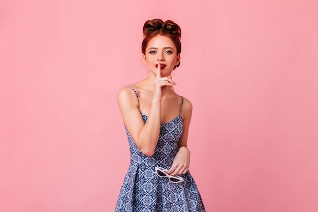 Neugieriges pinup-mädchen, das mit lächeln auf rosa raum aufwirft. studioaufnahme der bezaubernden dame, die lippen mit finger berührt.