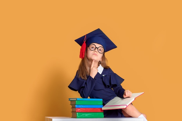 Neugieriges schulmädchen im abschlussoutfit, das mit lehrbüchern lernt