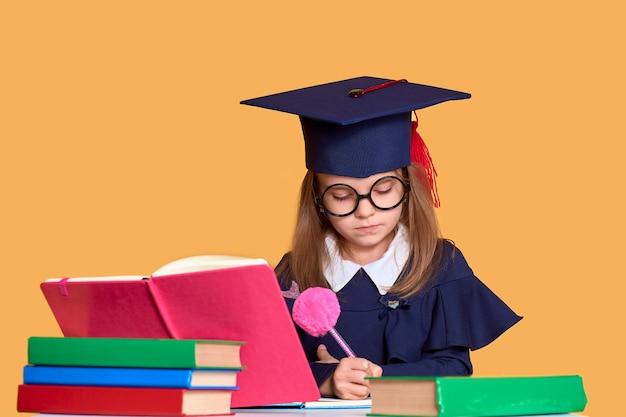 Neugieriges schulmädchen in der staffelungsausstattung studierend mit lehrbüchern