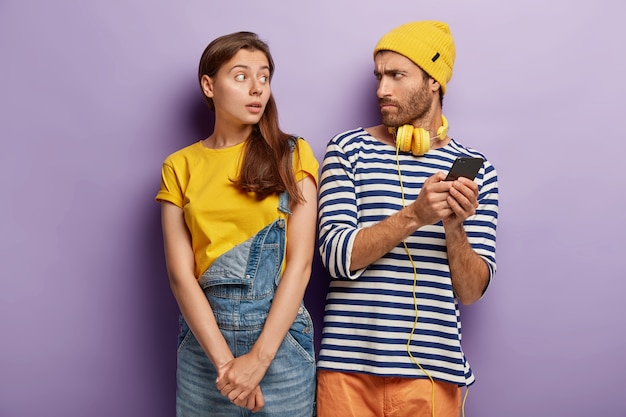 Neugieriges stilvolles paar, das mit smartphone aufwirft