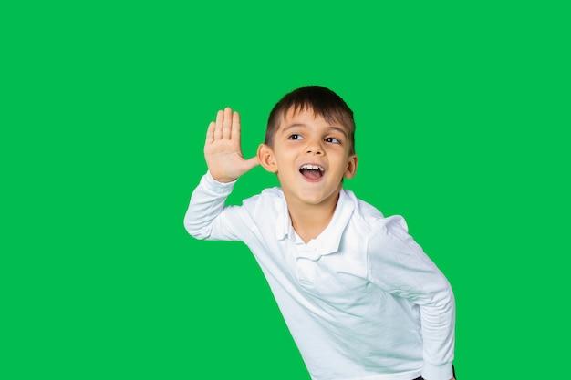 Neugieriges vorschulkind, das seine hand zum ohr hält und aufmerksam zuhört