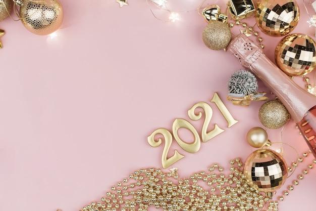Neujahr 2021 goldene zahlen im design der goldenen weihnachtsdekoration auf einem rosa.