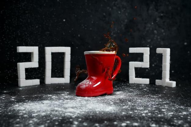 Neujahr 2021. kaffeespritzer und schnee kommen im kommenden 2021. zahlen aus zucker.