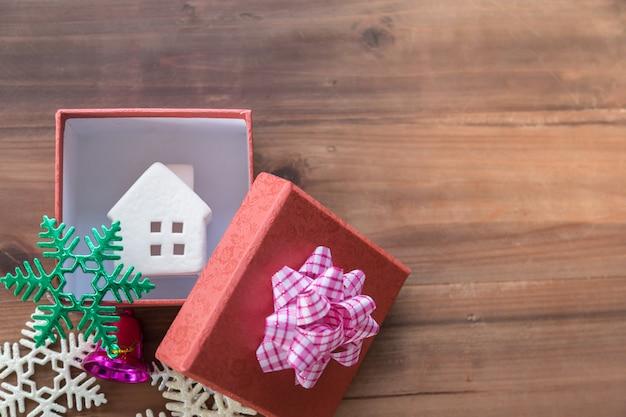 Neujahr, familie, weihnachten und holiday seasoning konzept. schließen sie oben von der hauptikone in der roten geschenkbox mit schönem band mit purpurroter glocke und bunten schneeverzierungen auf hölzerner planke mit kopienraum.