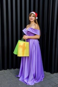 Neujahr feierlichkeiten. glückliche frau im modischen abendkleid mit bunten geschenktüten in weihnachtsmütze