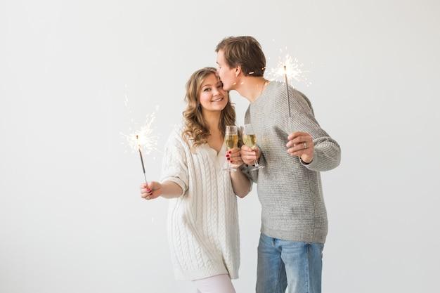 Neujahr, feiertage, datum und valentinstag-konzept - liebespaar, das wunderkerzenlicht und gläser champagner über weißer oberfläche hält