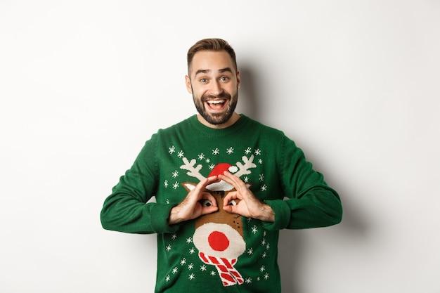 Neujahr, feiertage und feiern. glücklicher junger mann, der sich über seinen pullover lustig macht und lächelt, auf der weihnachtsfeier herumalbern und auf weißem hintergrund stehen