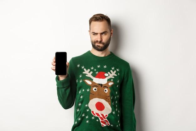 Neujahr, feiertage und feiern. skeptischer typ, der zweifelhaft auf den bildschirm schaut, während er es ihnen zeigt, die mobile app demonstriert und auf weißem hintergrund steht.