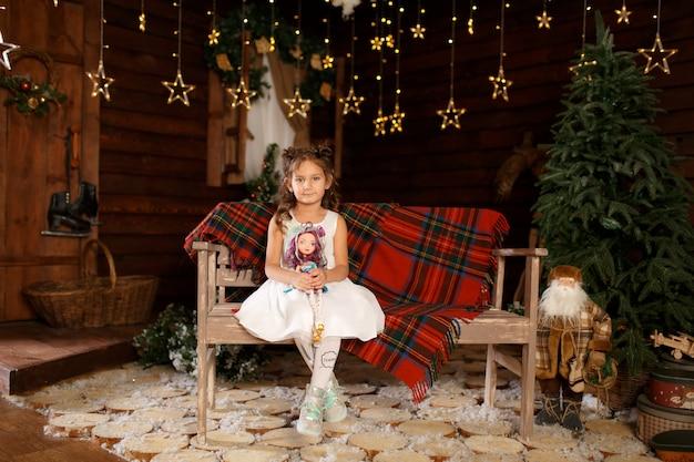 Neujahr . frohe weihnachten, schöne feiertage. ein kleines mädchen, das auf bank sitzt und puppe in den händen hält. magisches licht im nachtweihnachtsbaum-innenraum.