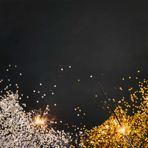 Neujahr hintergrund mit konfetti und wunderkerzen