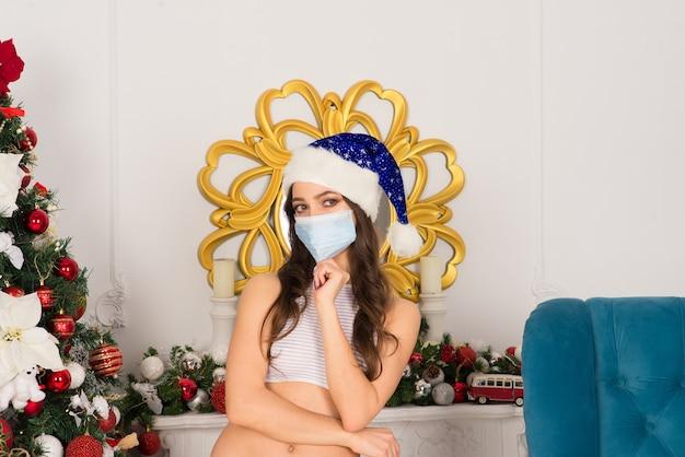 Neujahr. hübsche frau in weißen dessous, weihnachtsmütze und kovid schutzmaske, die drinnen nahe dem baum aufwirft