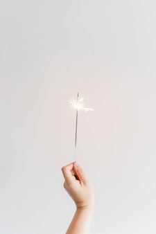 Neujahr komposition mit hand mit wunderkerze