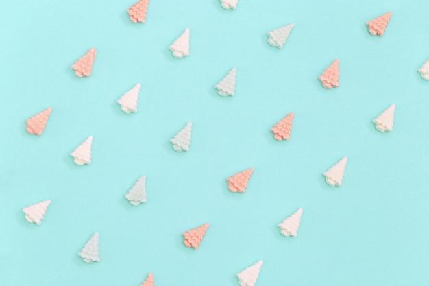 Neujahr oder weihnachten draufsicht pastell niedlichen süßigkeiten süßigkeiten, in form von weihnachtsbäumen liegen in reihen.