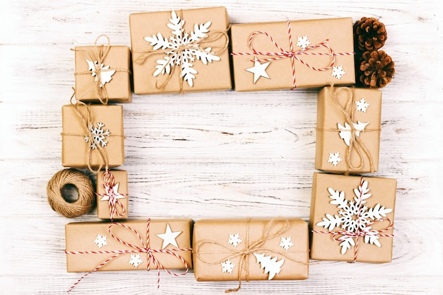 Neujahr und weihnachten frame zusammensetzung. handgemachte eingewickelte weihnachtsgeschenkboxen mit dekoration auf weiß mit leerem copyspace