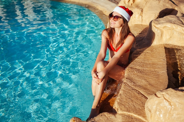 Neujahr und weihnachten. frau in sankt hut und in bikini, die im swimmingpool sich entspannen. tropische festferien