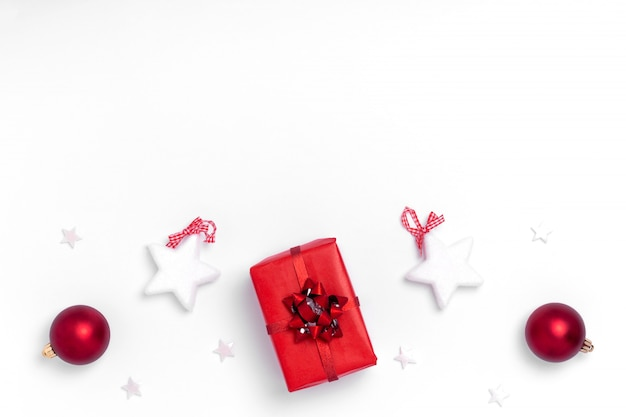 Neujahr und weihnachten komposition. feld von den roten bällen, von den weißen sternen, vom chrismas baum, von den rotwild und von den scheinen auf weißbuchhintergrund. draufsicht, flache lage, kopienraum