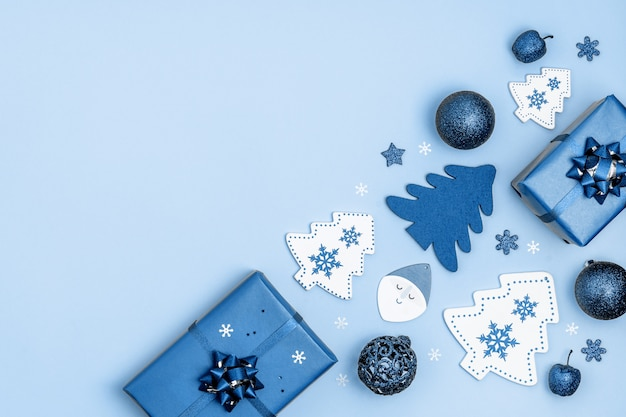 Neujahr und weihnachten rahmen. weihnachtsdekorationsgeschenkboxen, sterne, weihnachtsbaum, weihnachtsbälle, santa claus auf blau. draufsicht, flache lage, copyspace. trendige farbe des jahres.