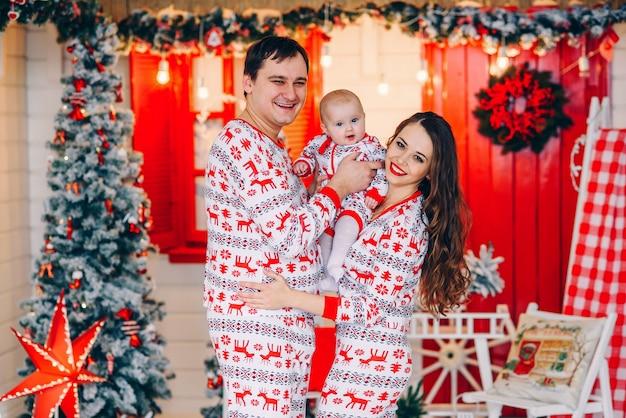 Neujahr und weihnachten urlaub konzept. eltern mit ihrer kleinen tochter in urlaubskleidung mit bedruckten hirschen und schneeflocken