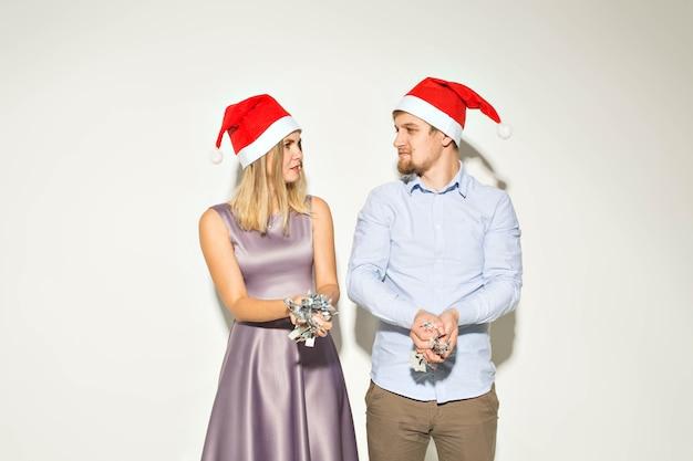 Neujahr, weihnachten und partykonzept - fröhliche junge leute geduscht mit konfetti auf weißem hintergrund.