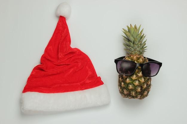 Neujahr, weihnachtskonzept. ananas gekleidet in gläsern mit weihnachtsmütze auf weißem hintergrund. draufsicht.