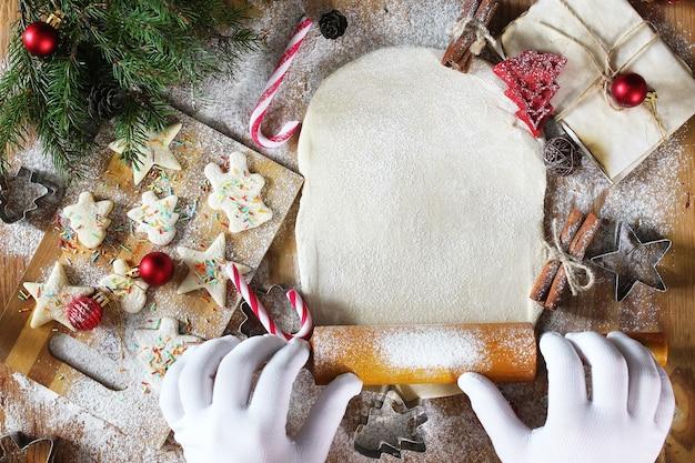 Neujahrs-delikatesse, die butterkekse in verschiedenen formen auf einem holztisch mit weihnachtszubehör kocht