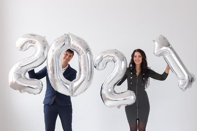 Neujahrs-, feier- und feiertagskonzept - liebespaar, das spaß mit zeichen 2021 aus silberballon hat