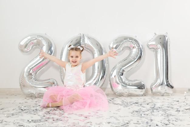 Neujahrs-, feiertags- und feierkonzept - kleines kindermädchen, das nahe mit zahlenballons sitzt