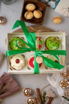 Neujahrs-geschenksets mit süßigkeiten. eine schachtel cupcakes als weihnachtsgeschenk. kuchen mit frischkäsecreme und erdnuss-karamell-füllung.