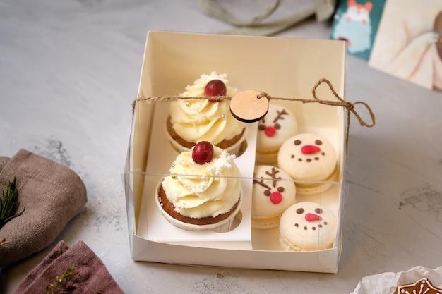 Neujahrs-geschenksets mit süßigkeiten. eine schachtel mit cupcakes und macarons als weihnachtsgeschenk. cupcakes mit frischkäsecreme und erdnuss-karamell-füllung und macarons-kuchen mit mandarinenfüllung.