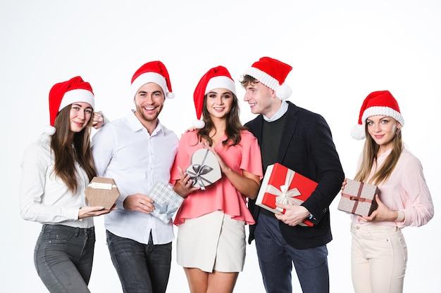 Neujahrs- oder weihnachtsfeier. gruppe junger leute in der weihnachtsmütze, die spaß hat