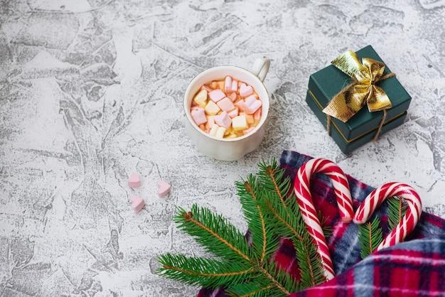 Neujahrs- oder weihnachtskomposition aus fichtengrünzweigen, plaid, neujahrsgeschenk, tasse mit süßigkeiten und lutschern