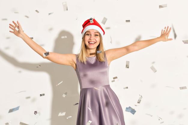 Neujahrs- und feiertagskonzept - glückliche aufgeregte junge frau im weihnachtsmann-hut, die über weißem hintergrund tanzt und lacht.