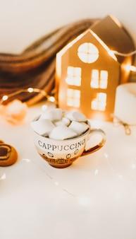 Neujahrs- und weihnachtshintergrund mit einer tasse kaffee mit marshmallows und kerzen auf weiß
