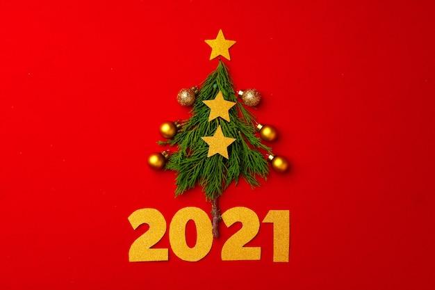 Neujahrs- und weihnachtshintergrund mit pelzbaumzweigen auf rotem hintergrund