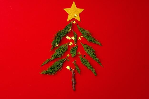 Neujahrs- und weihnachtshintergrund mit pelzbaumzweigen auf roter draufsicht