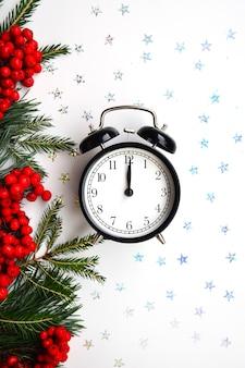 Neujahrs- und weihnachtskarte schwarzer vintage-wecker auf weißem hintergrund mit pailletten