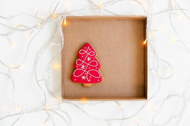 Neujahrs- und weihnachtslebkuchenplätzchen in der handwerklichen braunen schachtel mit licht. baumförmig. draufsicht. minimalistischer stil.