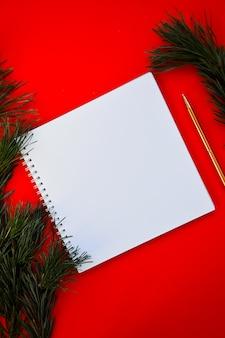 Neujahrs- und weihnachtsvorlage ein weißes notizbuch und ein goldener stift liegen auf rotem hintergrund