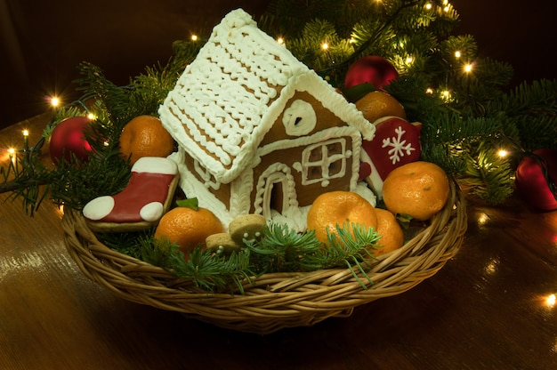 Neujahrs-weihnachtsplätzchen mit mandarinen und einem kleinen haus im korb