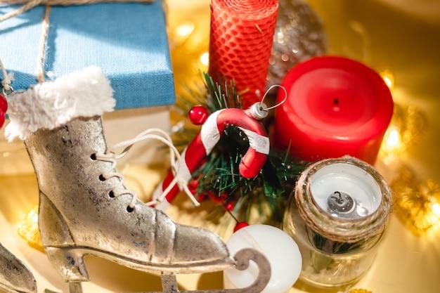Neujahrsatmosphäre neujahrsgeschenkkerze und weihnachtsspielzeuggirlande auf gelbem hintergrund