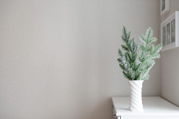 Neujahrsdekor minimalistische zusammensetzung der tannenzweige in der vase